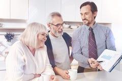 Vrai agent immobilier positif professionnel montrant le graphique aux couples pluss âgé photos libres de droits