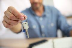Vrai agent immobilier remettant des clés aux clients image stock