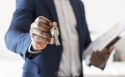 Vrai agent immobilier remettant la clé de maison photos stock