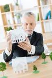 Vrai agent immobilier satisfaisant tenant une bonne miniature d'une vraie maison Photo stock