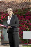 Vrai agent immobilier supérieur heureux regardant loin avec la maison à l'arrière-plan Photo libre de droits