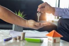 Vrai agent immobilier tenant la clé de maison sur son client après la signature photographie stock libre de droits