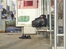 Vrai mendiant dormant sur l'arrêt d'autobus images libres de droits