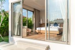 Vraie conception int?rieure de luxe dans la chambre ? coucher de la villa de piscine avec le lit confortable de roi avec la maiso image stock