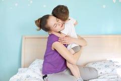 Vraie connexion d'enfant de dévotion et de mère La jeune maman européenne affectueuse embrasse son petit garçon, apprécie l'atmos image stock