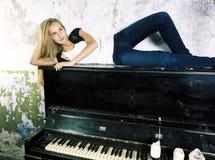 Vraie fille blonde assez jeune au piano dans l'int?rieur rouill? ? l'ancienne, concept de vintage photos stock