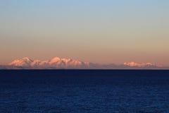 Vraie gamme de montagne de Cordillère au coucher du soleil derrière le lac Titicaca Photos stock