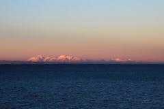 Vraie gamme de montagne de Cordillère au coucher du soleil derrière le lac Titicaca Image stock