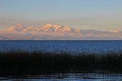 Vraie gamme de montagne de Cordillère au coucher du soleil derrière le lac Titicaca Photo libre de droits