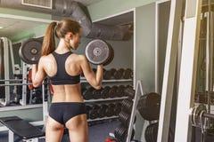Vraie jeune femme de forme physique pour presser l'haltère au-dessus de sa tête Photo stock