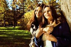Vraie mère mûre avec la fille en dehors de la chute d'automne en parc Photographie stock libre de droits