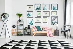 Vraie photo d'un divan avec des coussins et un betwe debout couvrant photographie stock libre de droits