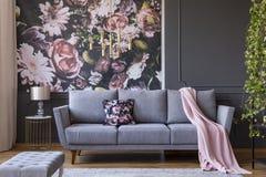 Vraie photo d'un intérieur de salon avec un sofa, un oreiller, une couverture et des fleurs sur le papier peint image libre de droits