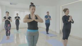 Vraies femmes se tenant tranquilles sur un tapis de pilates et faisant le yoga dans un studio de forme physique - clips vidéos