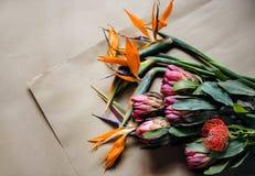 Vraies fleurs tropicales fraîches sur le fond de métier de papier de Brown photos stock