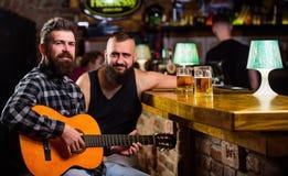 Vrais loisirs d'hommes Guitare de jeu d'homme dans la barre Les amis gais détendent avec la musique de guitare Relaxation de vend images stock