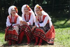 People in traditional authentic folklore costume a meadow near Vratsa, Bulgaria. Vratsa, Bulgaria - June 24, 2018: People in traditional authentic folklore stock image