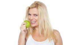 Vård- medveten kvinna omkring som tar tuggan från det gröna äpplet Arkivfoton