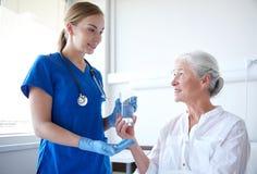Vårda att ge medicin till den höga kvinnan på sjukhuset Fotografering för Bildbyråer
