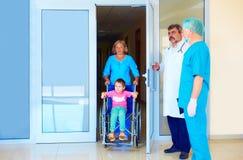 Vårda att ta omsorg av den lilla patienten i rullstol i sjukhus Arkivfoton