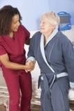 Vårda den höga kvinnan för portionen ut ur säng i sjukhus Arkivbild