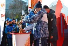 Vårdare av branden på den olympiska facklarelän i Sochi Arkivfoto