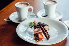 Vrede van gelaagd soufflédessert met chocoladesaus op plaat, op houten lijst stock afbeeldingen
