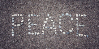 'Vredes' woord op het zand Geschreven met kiezelstenen Oude foto Stock Foto