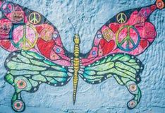 vredesconcepten over vlinder het schilderen op grungemuur die worden geschilderd stock foto's