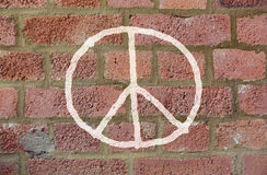 Vredesteken die op rode bakstenen muur trekken Stock Afbeeldingen