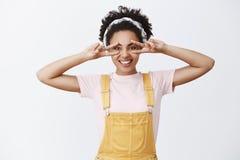 Vredesvrienden Aantrekkelijke donker-gevilde modieuze vrouwelijke vriend in hoofdband over haar en gele in overall, het tonen stock afbeelding
