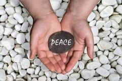 Vredeswoord in steen op hand stock afbeeldingen