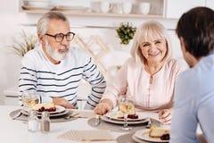 Vreedzaam bejaard paar die diner met hun jong geitje thuis smaken Royalty-vrije Stock Foto