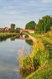 Vreedzaam Kanaal en Tow Path met Kleine Baksteenbrug Stock Foto