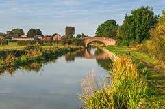 Vreedzaam Kanaal en Tow Path met Kleine Baksteenbrug Royalty-vrije Stock Afbeeldingen