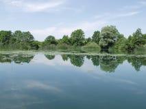 Vreedzaam meer met wolken die in water worden weerspiegeld Stock Afbeeldingen