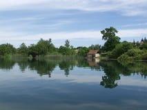 Vreedzaam meer met wolken die in water worden weerspiegeld Stock Foto