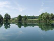 Vreedzaam meer met wolken en bomen die in water worden weerspiegeld Stock Foto