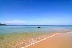 Vreedzaam strand met boot stock afbeelding