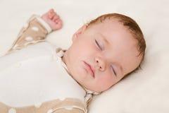 Vreedzame baby die op een bed liggen terwijl het slapen Stock Afbeelding