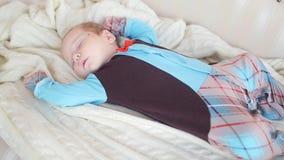 Vreedzame baby die op een bed liggen terwijl het slapen stock videobeelden