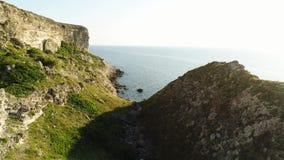 Vreedzame blauwe overzees en vers groen gras van een rotsachtige helling bij het kustschot Magische weg aan het eindeloze overzee stock videobeelden