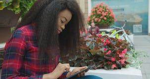 Vreedzame gang van het aantrekkelijke jonge Afrikaanse meisje die, en via de tablet doorbladeren texting terwijl openlucht zitten stock video