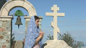 Vreedzame jonge vrouw die in openlucht dichtbij steenkruis bidden, die God om zegen vragen stock video
