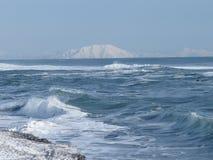 Vreedzame Oceaan, golven en meningen van de snow-covered heuvel in de winter in zonnig weer in Kamchatka, Rusland stock foto's