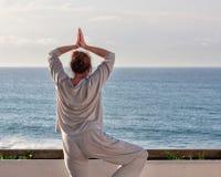 Vreedzame Oceaan, vrouwenoefening die op het terras ademen Royalty-vrije Stock Foto's