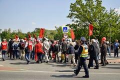 Vreedzame optocht van mensen met rode vlaggen en ballons op de hoofdstraat royalty-vrije stock afbeeldingen