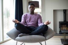 Vreedzame Tiener die Zitting als Voorzitter thuis mediteren royalty-vrije stock foto's