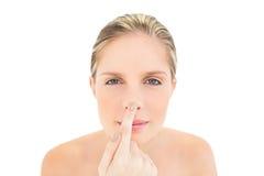 Vreedzame verse blondevrouw wat betreft haar neus Stock Foto's