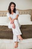 Vreedzame vrij bruine haired vrouwenzitting op een bed Stock Foto's